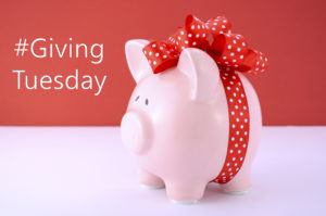 Gift wrapped piggy bank on red white background for Giving Tuesday savings concept.