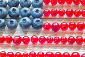 Patriotic American flag cake with blueberries and red currant on vintage wooden background